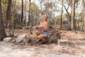 Girl laughing with kangaroos